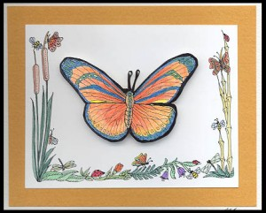 The three sided frame of cattails, bamboo and bugs is stamped. One butterfly is stamped inside this frame.